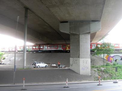 Die S-Bahn unter der Langenfelder Autobahnbrücke und ein einzelner Bauarbeiter auf der Baustelle