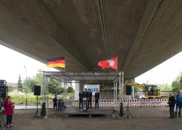 Die beflaggte Bühne mit Rednerpult, rechts dahinter wartet der Bagger auf seinen Einsatz